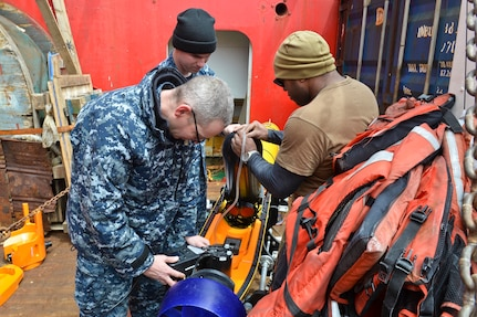 Technicians perform maintenance on an unmanned underwater vehicle.