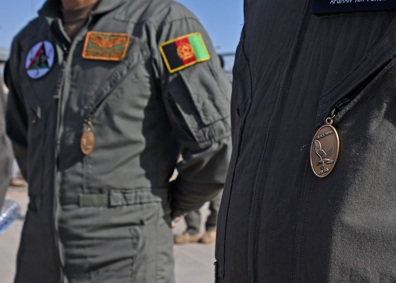 Afghan Air Force pilots wear Black Hawk pendants given by instructors signifying their completion of UH-60 Black Hawk training at Kandahar Airfield, Afghanistan, Nov. 20, 2017. The pilots are the first six to become AAF UH-60 pilots. The pilots have prior experience in the Mi-17 Hip. The transition of airframe for the AAF pilots will provide firepower and mobility, significant offensive factors enabling the Afghan National Defense and Security Forces to break the stalemate with insurgents. (U.S. Air Force photo by Tech. Sgt. Veronica Pierce)