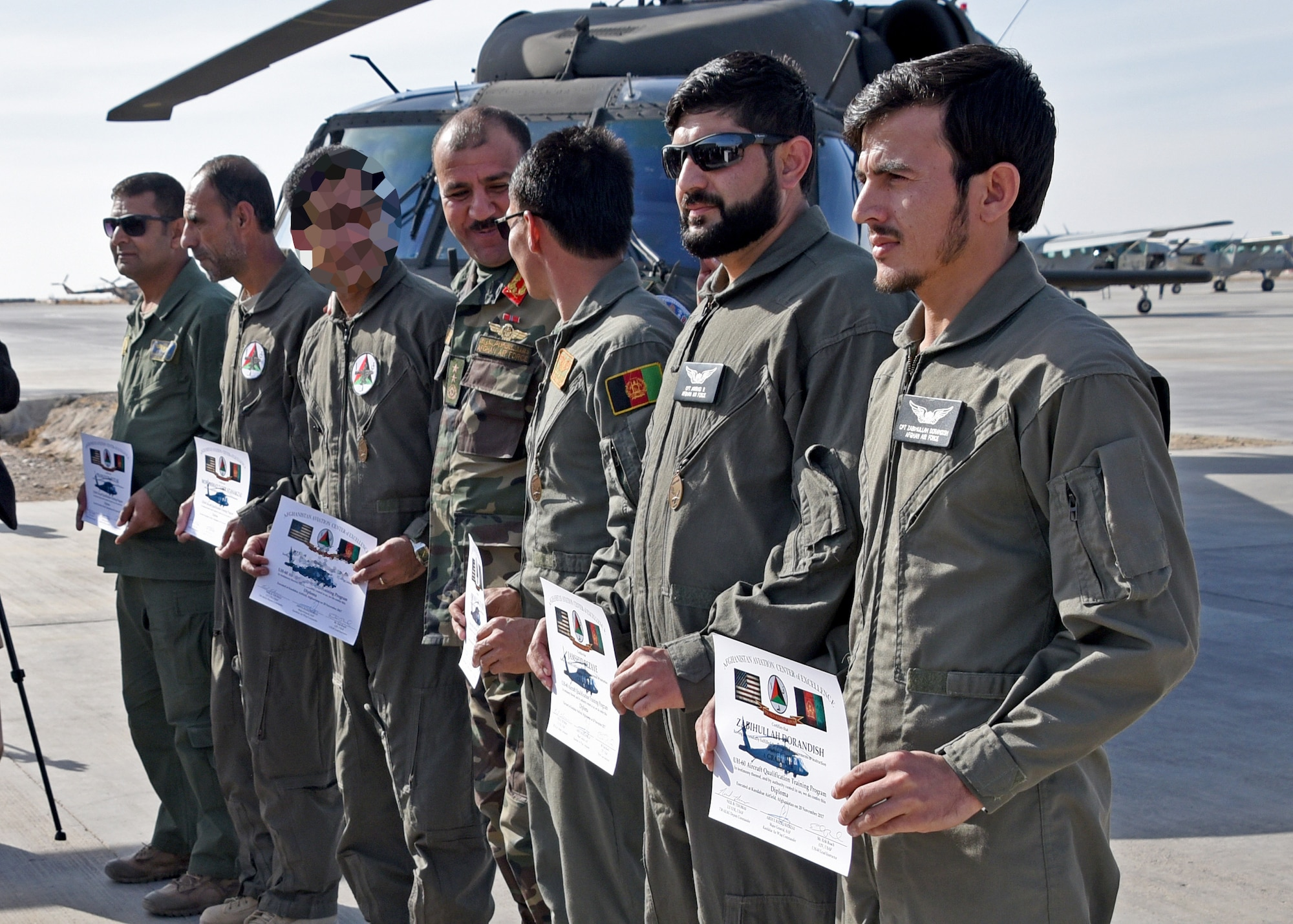 Afghan Air Force pilots display their certificates after a UH-60 Black Hawk Aircraft Qualification Training graduation ceremony at Kandahar Airfield, Afghanistan, Nov. 20, 2017. The six pilots are the first AAF Black Hawk pilots, is part of a larger modernization program. The Afghan Air Force will more than double their fleet of aircraft over the next seven years. Plans include the introduction of AC-208 attack aircraft and UH-60 Black Hawk assault helicopters, and additional A-29 attack aircraft and MD-530 attack helicopters to the force. (U.S. Air Force photo by Tech. Sgt. Veronica Pierce)