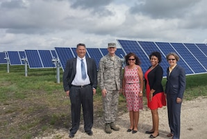 Stakeholders stand in front of solar panels