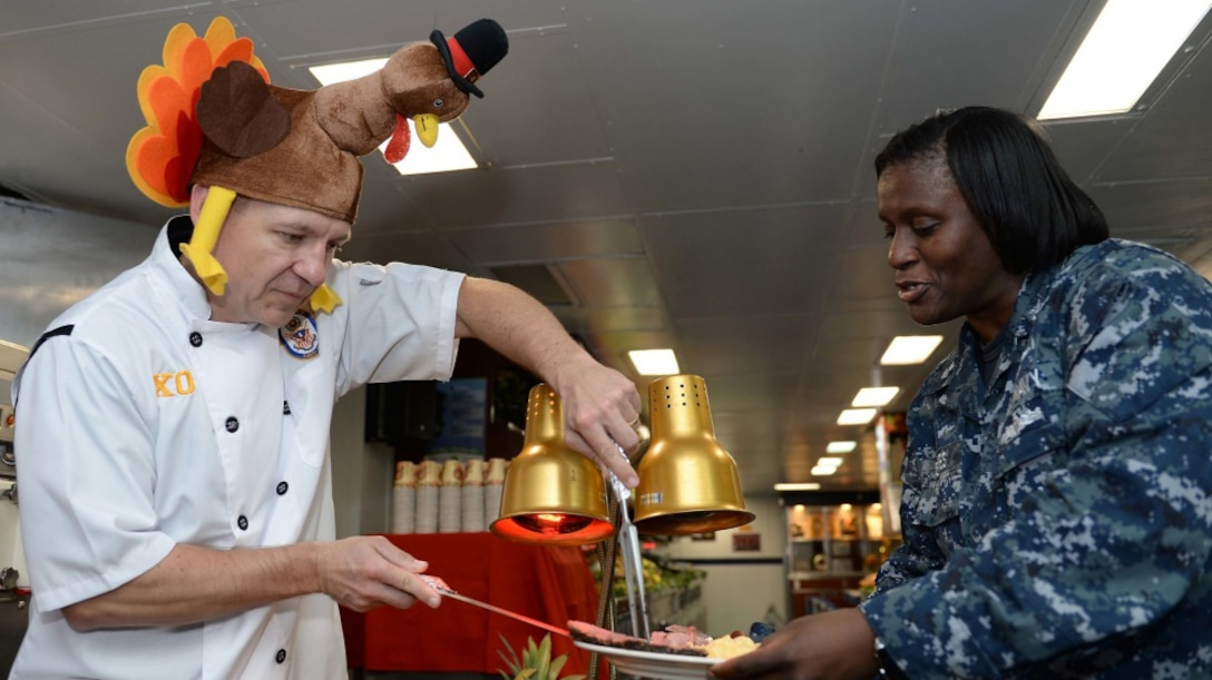 A man wearing a turkey hat serves meat to a female service member.