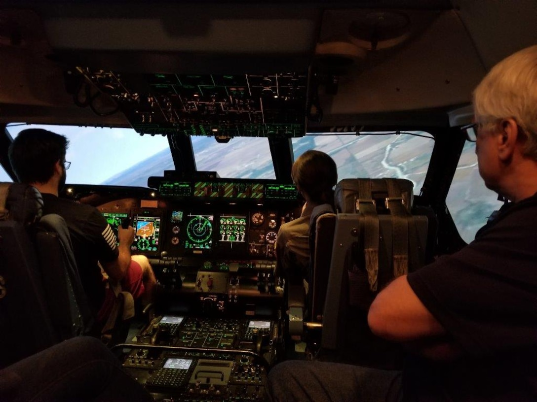 A group of honorary commanders and civic leaders got to experience flight in the C-5M Super Galaxy Simulator, during the 433rd Operations' Group tour, Nov. 18, 2017, on Joint Base San Antonio, Texas. Alex Ridolfi, is in the driver's seat of the C-5M Simulator, with instructor Major Brandi Cone in the instructor's seat, while Simulator Instructor, Steve Bilyeu oversees the whole operation. (U.S. Air Force photo by Minnie Jones)