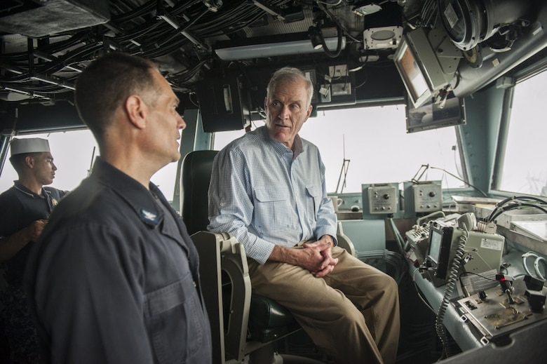Secretary of the Navy Richard V. Spencer speaks to Capt. Joseph Olson, the commanding officer of the amphibious assault ship USS America, on the bridge during his visit on Thanksgiving Day.