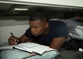 Navy Petty Officer 3rd Class Antwoun Stevens writes poetry in his rack aboard the guided-missile cruiser USS Lake Erie, Oct. 19, 2017. Navy photo by Petty Officer 3rd Class Lucas T. Hans