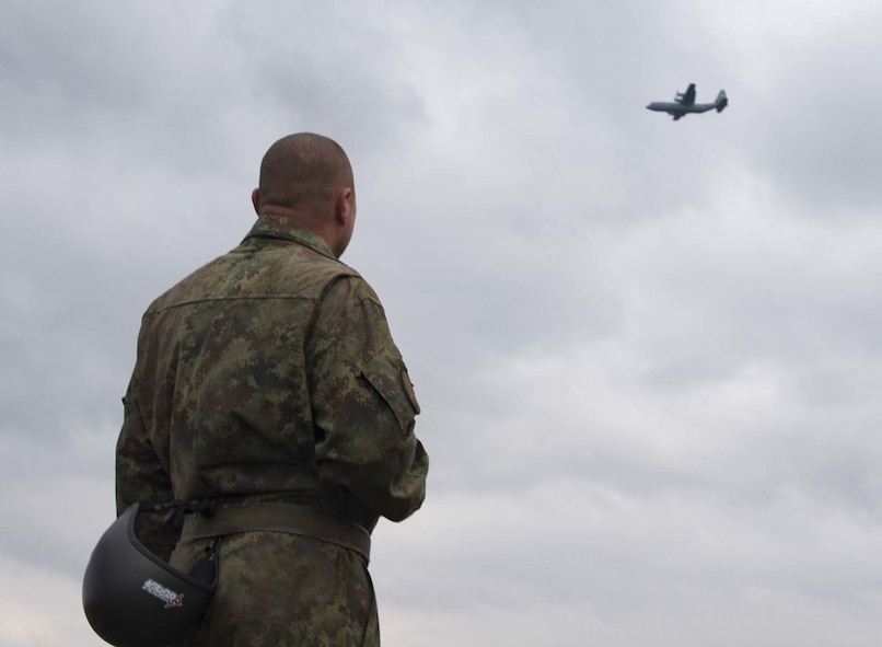 A Serbian jumper observes a C-130J assigned to the 37th Airlift Squadron after landing in Kovin, Serbia on November 16, 2017. Serbian and U.S. paratroopers jumped together in Exercise Double Eagle, a bi-lateral airborne insertion exercise designed to allow U.S. and Serbian forces to work together in areas of mutual interest in securing regional security and peace.