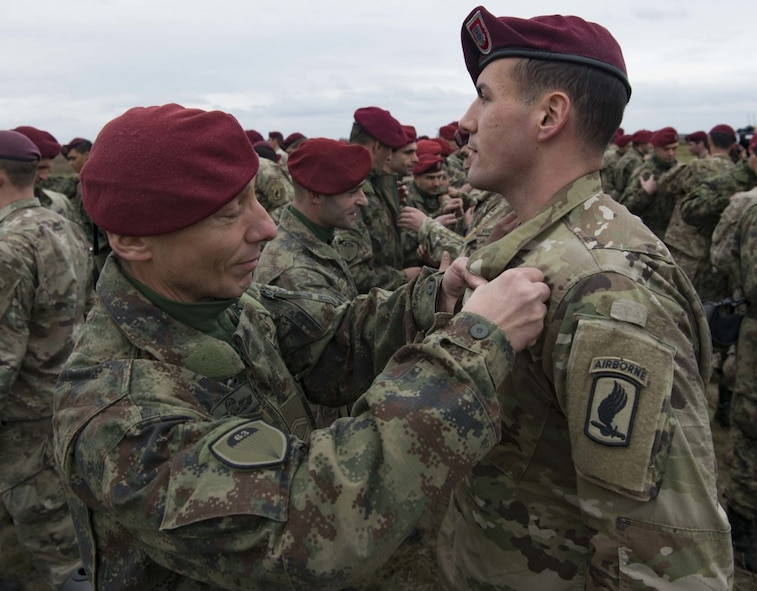 A Serbian paratrooper trades jump wings with a U.S. Army paratrooper assigned to the 173rd Airborne Brigade on Lisicji Jarak Airport, Serbia, Nov. 17, 2017. U.S. and Serbian paratroopers traded jump wings as a symbol of goodwill after conducting five days of airborne insertion exercises together during Exercise Double Eagle. (U.S. Air Force photo by Senior Airman Elizabeth Baker)
