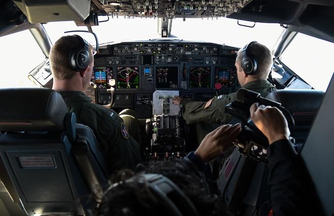 Pilots fly a P-8a Poseidon aircraft.