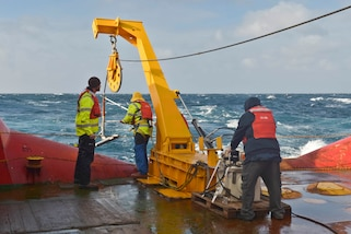 Argentine sailors retrieve side scanning sonar equipment on board a ship.