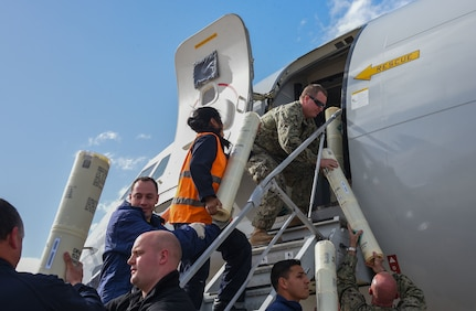 Sailors load sonobouys onto a P8-A Poseidon aircraft.