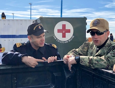 A US Navy and Argentine navy officer talk.
