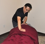 Oliver Huang rubs the back of a client during a massage.