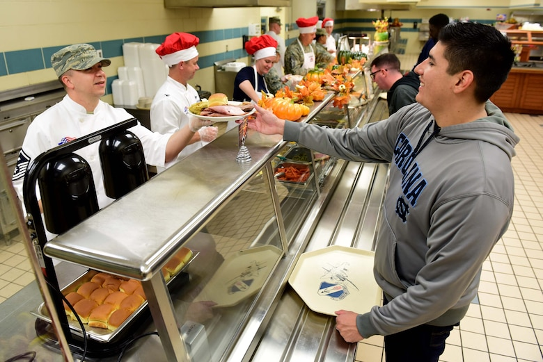 Master Sgt. Joshua McLaughlin, 4th Force Support Squadron first sergeant, serves a meal to Airman Christian Ramirez, F-15E Strike Eagle student crew chief, at the 4th FSS dining facility Nov. 23, 2017, at Seymour Johnson Air Force Base, North Carolina. Base leaders helped serve more than 150 meals to dining facility guests on Thanksgiving Day. (U.S. Air Force photo by Airman 1st Class Kenneth Boyton)