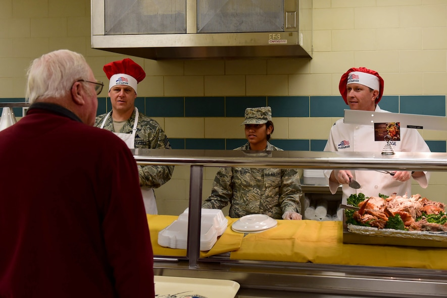 Col. Christopher Sage, 4th Fighter Wing commander, right; Airman 1st Class Kristal Montalvo, 4th Force Support Squadron food service worker, center and Chief Master Sgt. William Adams, 4th FW command chief, left, help serve a Thanksgiving holiday meal to Airmen and dining facility attendees at the Seymour Johnson Air Force Base 4th FSS dining facility Nov. 23, 2017, at Seymour Johnson AFB, North Carolina. Base leaders helped serve more than 150 meals to dining facility guests on Thanksgiving Day.  (U.S. Air Force photo by Airman 1st Class Kenneth Boyton)