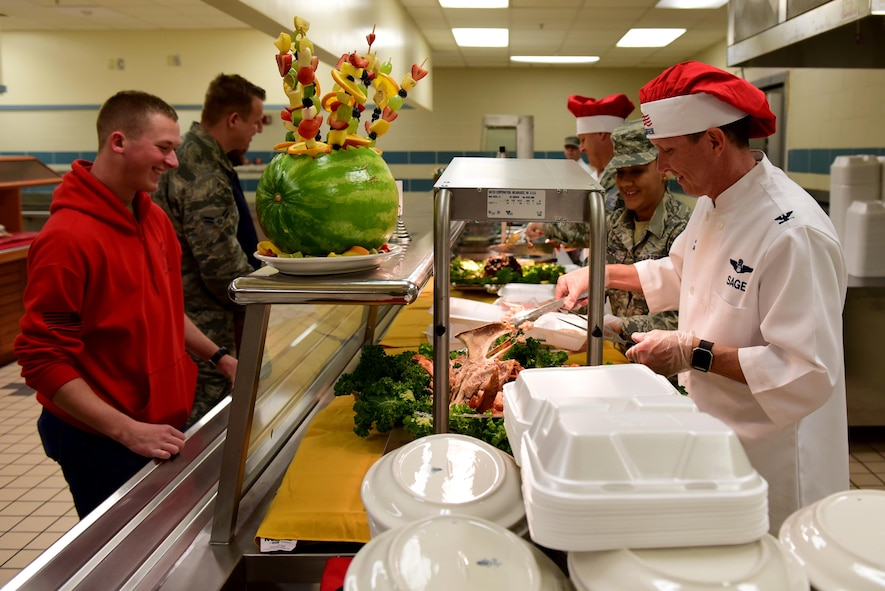 Col. Christopher Sage, 4th Fighter Wing commander, serves turkey to Airman Luke Heinl, F-15E Strike Eagle student crew chief, at the 4th Force Support Squadron dining facility Nov. 23, 2017, at Seymour Johnson Air Force Base, North Carolina. Base leaders helped serve more than 150 meals to dining facility guests on Thanksgiving Day. (U.S. Air Force photo by Airman 1st Class Kenneth Boyton)