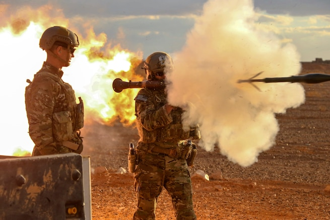 Two soldiers fire a weapon.