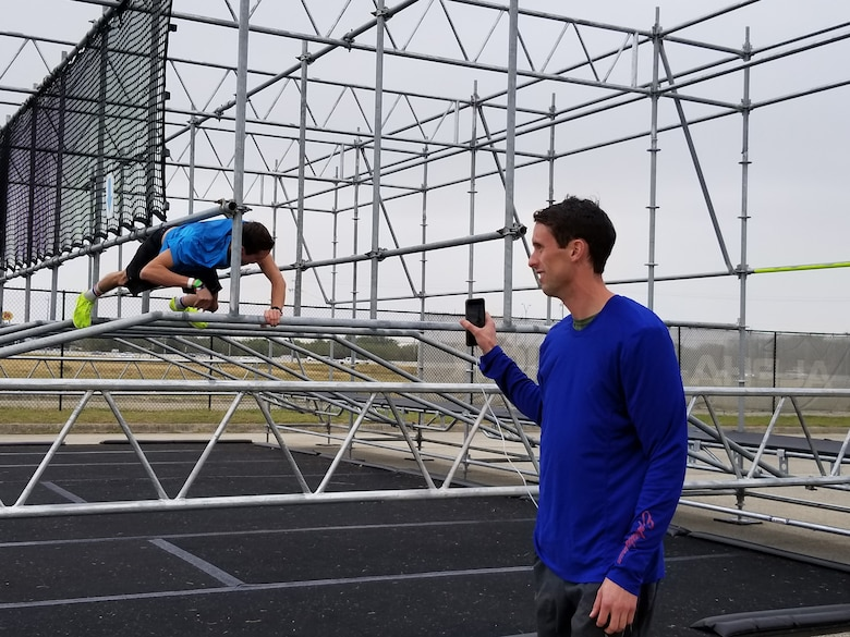 .S. Air Force Capt. Rob Simmons tackles the Gut Buster obstacle on the Alpha Warrior Battle Rig at Retama Park in Selma, Texas, as his identical twin brother, Capt. Cale Simmons, shoots video. Cale placed second in the men's division in the Air Force Alpha Warrior Final Battle on Nov. 11, 2017. (U.S. Air Force photo by Carole Chiles Fuller)