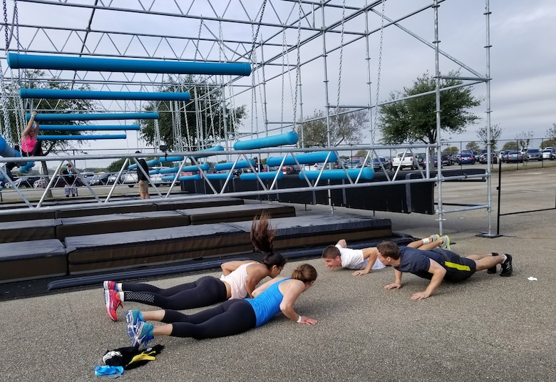 Capt. Lesly Palicia, back left, performs a set of burpees after falling at the Battering Rams obstacle with the support of fellow Air Force Alpha Warrior competitors Capts. Rachel Schaefer. Noah Palacia and Jeff Schaefers. The couples were on the U.S. Air Force Academy track team together. (U.S. Air Force photo by Carole Chiles Fuller)
