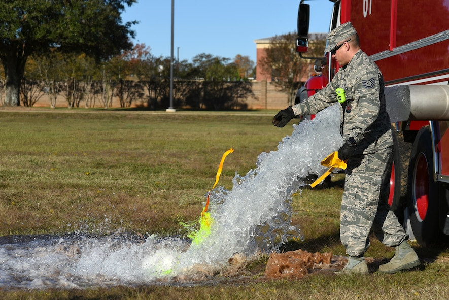 U.S. Air Force Tech. Sgt. Larry Diaz, 20th Civil Engineer Squadron noncommissioned officer in charge of training, tosses a dye packet into water being emptied from a fire truck during a major accident response exercise at Shaw Air Force Base, South Carolina, Nov. 17, 2017.