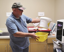 Barry Maples, environmental compliance inspector with the Directorate of Public Works - Environmental Division, holds a container with hazardous waste materials inside during a routine inspection Oct. 13 in the Women's Health Clinic at Irwin Army Community Hospital.
