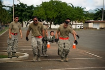 Members of the 48th Aerial Port Squadron perform a litter carry during the combat fitness challenge portion of the Hickam Port Dawg Challenge, at Joint Base Pearl Harbor-Hickam, Hawaii, Nov. 17, 2017.
