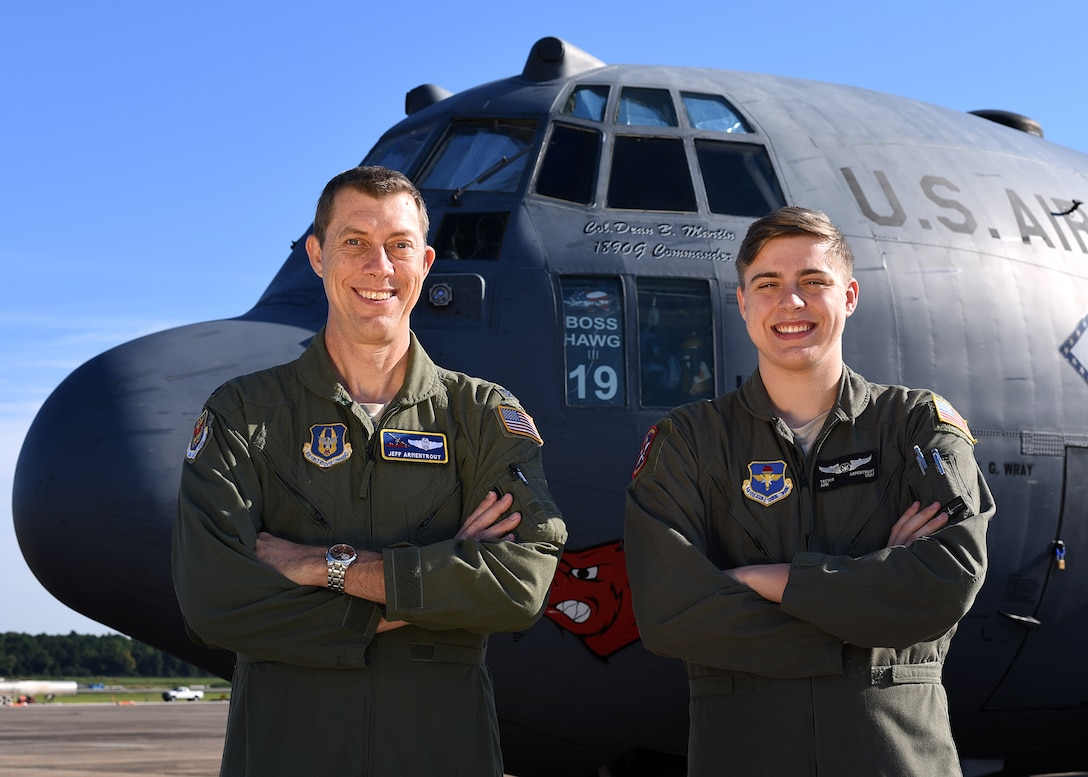 A father and son pose for a photo in front of a C-130 on a flightline.