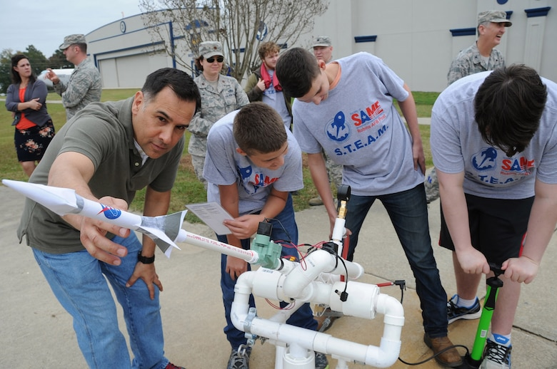 John Cockrell of Air Force Reserve Command's Directorate of Logistics, Engineering and Force Protection helps Jasper County High School students prepare their paper rocket for launch. (Matt Ebarb)