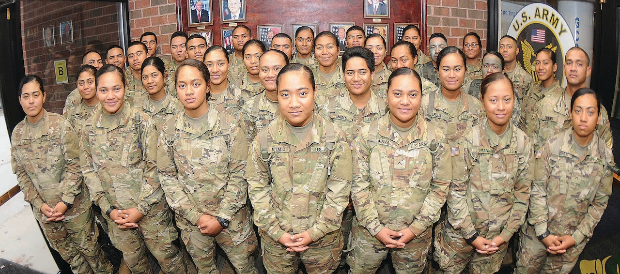 More than 30 members of an American Samoa family pose for pictures at Thompson Hall, Fort Lee, Va., Nov. 8, 2017. The soldiers are advanced individual training students, and most are enrolled in the Unit Supply Specialist Course taught by the Quartermaster School. In all, 41 members of the same Samoan family are training at Fort Lee. Army photo by Terrance Bell
