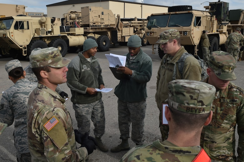 Members of the 97th Air Mobility Wing and the 4th Battalion, 3rd Air Defense Artillery Regiment prepare to inspect several vehicles during a joint exercise