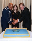 Lt. Col. Christopher Robinson, 91st Cyberspace Operations Squadron commander, Alyssa Correia, and John Reynolds III participate in the formal cutting of the cake during the 91st COS centennial dinner in San Antonio, Oct. 28, 2017. Reynolds is a surviving descendant of the 91st COS' founding commander, Col. John Reynolds. (Courtesy photo)