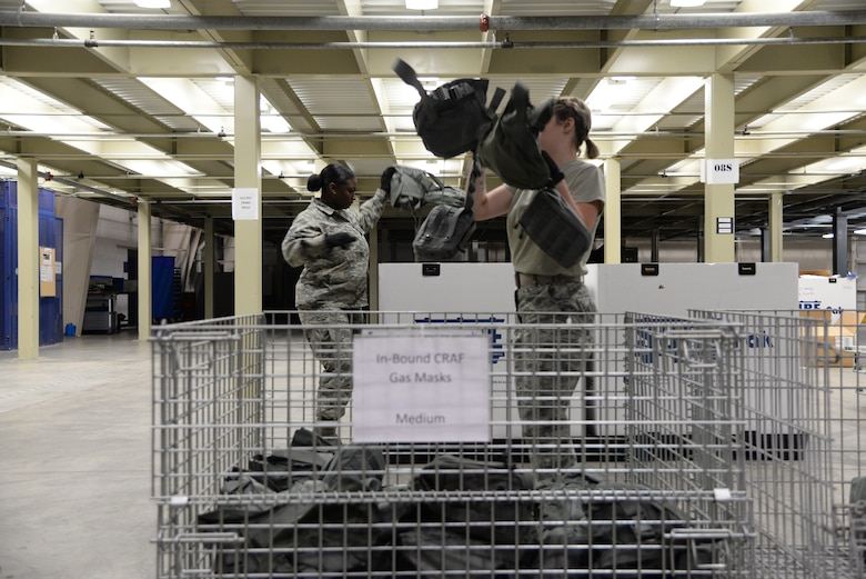 Tech. Sgt. Deanna Parsons, 436th Logistics Readiness Squadron NCO in charge of individual protective equipment, and Airman 1st Class Alizabeth Rawlings, 436th LRS materiel management technician, transfer gas masks to containers during a Civil Reserve Air Fleet readiness exercise Nov. 13, 2017, inside the IPE warehouse on Dover Air Force Base, Del. They maintained accountability for every piece of equipment ensuring no items were lost or unaccounted for. (U.S. Air Force photo by Staff Sgt. Aaron J. Jenne)