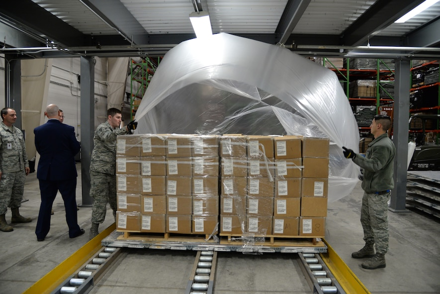 Airmen 1st Class Matthew Moneymaker-Grizzle and Ryan Chamberlain, 436th Aerial Port Squadron cargo processors, prepare a pallet of gas masks during a Civil Reserve Air Fleet readiness exercise Nov. 13, 2017, at Dover Air Force Base, Del. Each pallet was covered in plastic to protect it from the elements and strapped down to secure the contents for flight. (U.S. Air Force photo by Staff Sgt. Aaron J. Jenne)