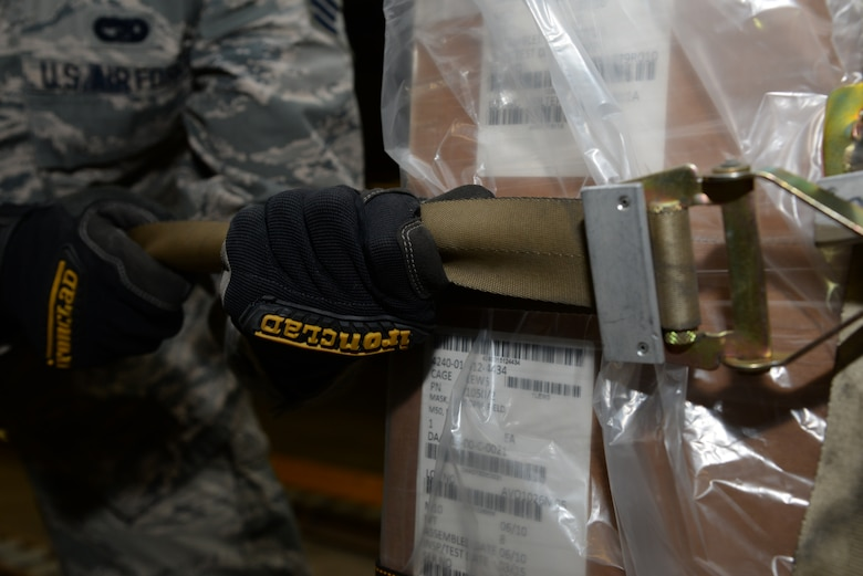 A member of the 436th Aerial Port Squadron cinches a strap on a pallet during a Civil Reserve Air Fleet readiness exercise Nov. 13, 2017, inside the individual protective equipment warehouse on Dover Air Force Base, Del. Members of the 436th APS strapped down the pallets of IPE gear and transported it to a staging area to prepare for flight. (U.S. Air Force photo by Staff Sgt. Aaron J. Jenne)