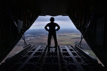 Senior Airman Megan Nelson, 41st Airlift Squadron instructor loadmaster, gazes over Arkansas landscape Nov. 21, 2017. Nelson used her time in the air to help train the Airmen with her on how to properly drop aerial delivery cargo. (U.S. Air Force photo by Airman 1st Class Rhett Isbell)