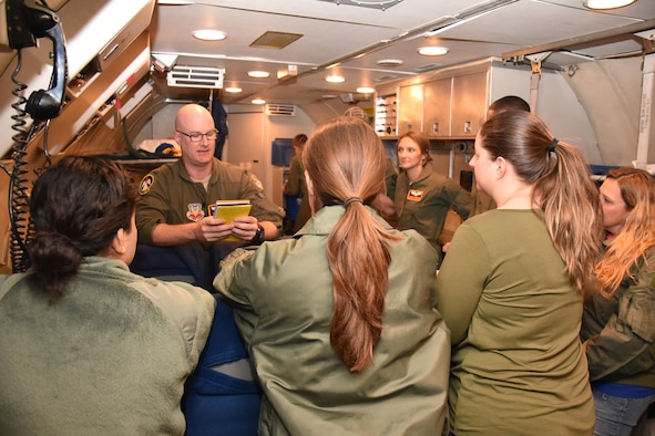 An aircrew member with the 964th Airborne Air Control Squadron gives a safety briefing prior to take off to a group of spouses participating in a spouse orientation flight on the E-3 Sentry aircraft 28 Nov. 2017.