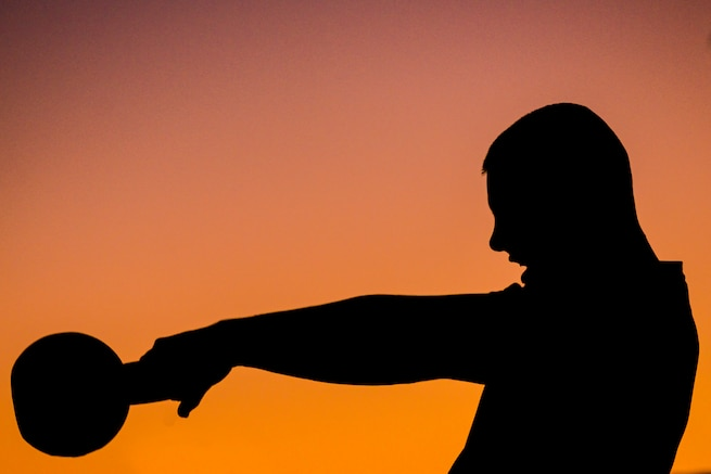 A silhouette of a person with workout equipment is against a colorful sky.