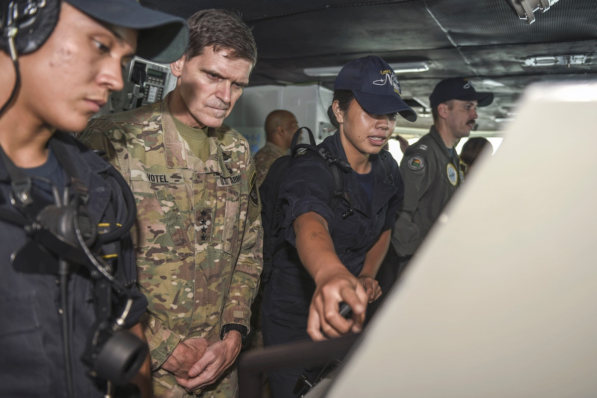 The commander of U.S. Central Command visits with sailors on a ship.