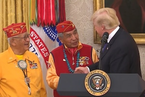 President Donald J. Trump shakes hands with two Navajo Code Talkers from behind a podium.