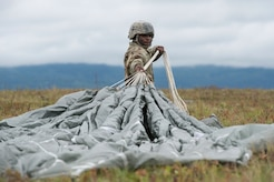 A paratrooper assigned to 2nd Battalion, 377th Parachute Field Artillery Regiment, 4th Infantry Brigade Combat Team (Airborne), 25th Infantry Division, U.S. Army Alaska, recovers his parachute after conducting airborne jump training at Malemute drop zone, Joint Base Elmendorf-Richardson, Alaska, Aug. 24, 2017.