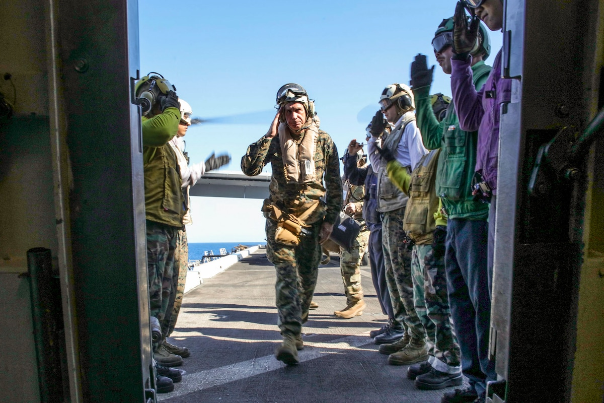 The commander of U.S. Africa Command salutes sideboys as he arrives on a ship.