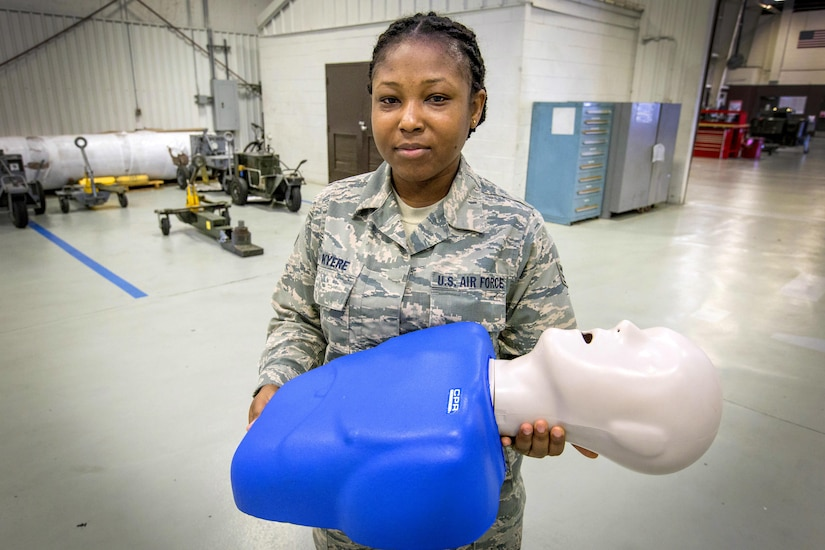 A woman poses for a photograph holding a CPR mannequin in a large room.