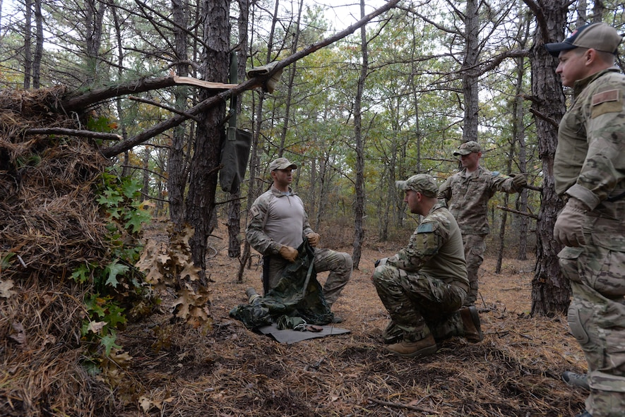 Senior Airman Alexander Triani, a pararescueman with the 103rd Rescue Squadron of the 106th Rescue Wing assigned to the New York Air National Guard, demonstrates how to make a mattress from a used parachute in the woods of Westhampton Beach, New York November 1, 2017.
