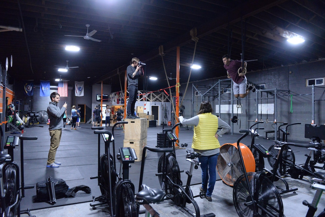 The crew from Futures magazine watch as Senior Airman Alexander Triani, a pararescueman with the 103rd Rescue Squadron of the 106th Rescue Wing assigned to the New York Air National Guard, is photographed doing muscle-ups at a CrossFit Gym in Bayport New York November 1, 2017.