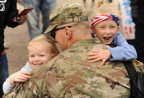 Army Staff Sgt. Keith Fitzgerald hugs his family in Huron, S.D., after returning from a 10-month deployment to the Middle East.