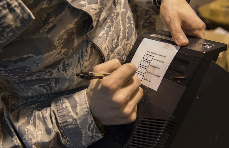 U.S. Air Force Tech. Sgt. James Providenti, 130th Communications Flight Supervisor, signatures a box showing hard drive removal on a computer Nov. 28, 2017 at McLaughlin Air National Guard Base, Charleston, W.Va.