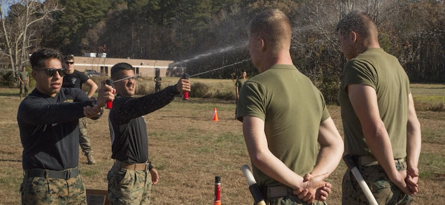 Staff Sgt. Omar Guzman, staff non-commissioned officer in charge, left, and Sgt. Brandon Bedard, instructor, Basis Security Guard Course, Training Co., U.S. Marine Corps Security Forces Regiment, spray oleoresin capsicum in the faces of students during the Level 1 OC Contamination Course at Naval Support Activity Northwest Annex, Chesapeake, Va., Nov. 28. Instructors were required to have OC training before being certified to use it on the students. (Official U.S. Marine Corps photo by Chris Jones/Released)