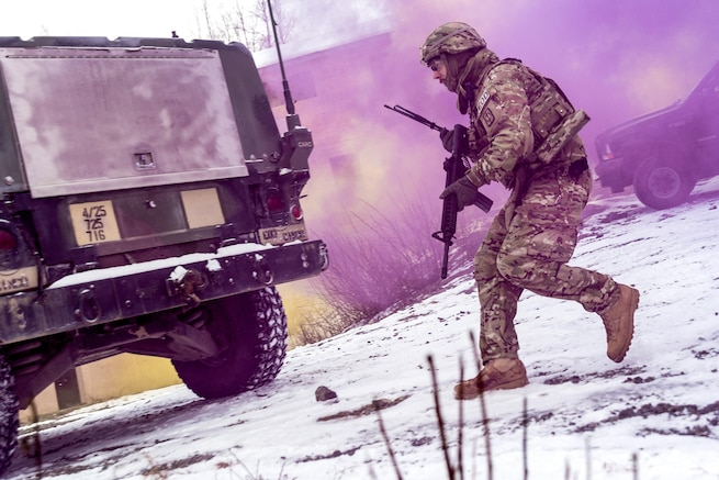 A soldier runs towards a vehicle with purple smoke in the air.