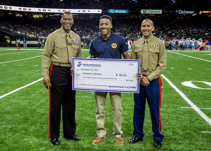 Major General Craig C. Crenshaw, Commanding General of Marine Corps Logistics Command, left, and Maj. William T. Kerrigan, Commanding Officer of Recruiting Station Baton Rouge, present Cameron Johnson, a student at Southern University, the Frederick C. Branch Leadership Scholarship check during the Bayou Classic football game at the Mercedes-Benz Superdome in New Orleans, LA, Nov. 25, 2017. The scholarship is presented to students who display exemplary leadership and academic achievement. The Bayou Classic offered the Marine Corps the opportunity to showcase the importance of music through sponsorship. (U.S. Marine Corps photo by Lance Cpl. Jack A. E. Rigsby/Released)