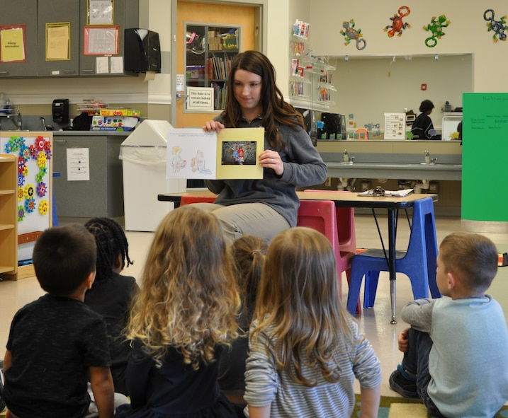 """Avery Tibbets, daughter of Brig. Gen. Paul W. Tibbets IV, deputy commander, Air Force Global Strike Command, reads her book """"While Daddy's Away,"""" to preschool-aged children at the Child Development Center at Barksdale AFB, Louisiana. (U.S. Air Force photo/Joe Thomas)"""