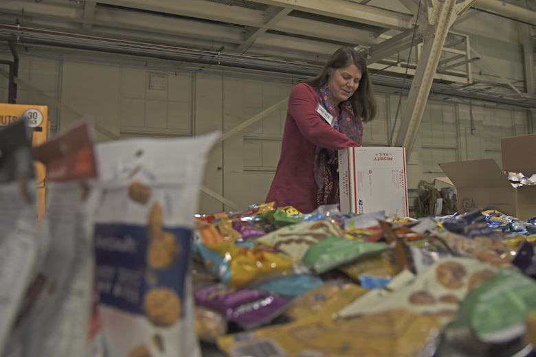 Kelley Cargle, Officer Spouses' Club vice president of operations, packs a Treats 2 Troops care package with snacks Nov. 29, 2017, at Fairchild Air Force Base, Washington. KREM 2 News began collecting donations the beginning of November and collected thousands of items in less than a month to benefit military members serving overseas during the holiday season. (U.S. Air Force photo/Senior Airman Mackenzie Richardson)