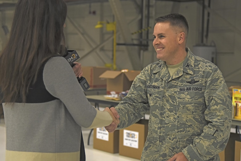 Col. Scot Heathman, 92nd Air Refueling Wing vice commander, talks with KREM 2 News anchor, Laura Papetti, about the benefits of the Treats 2 Troops initiative during a live interview Nov. 29, 2017, at Fairchild Air Force Base, Washington. KREM 2 News partnered with Team Fairchild for the seventh year in a row to fill care packages with small treats and gifts to help benefit military members serving overseas during the holiday season. (U.S. Air Force photo/Senior Airman Mackenzie Richardson)